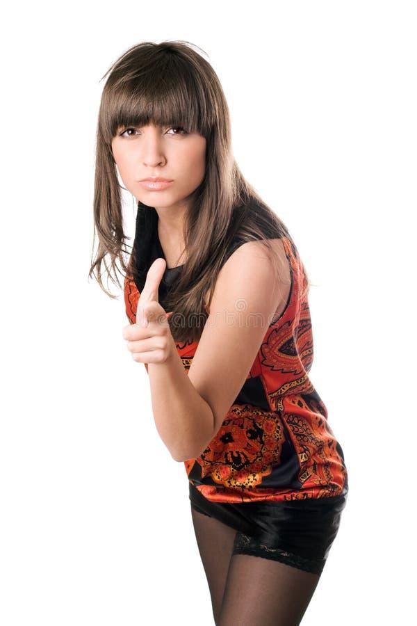 Όμορφο brunette που δείχνει το δάχτυλό της στοκ εικόνα