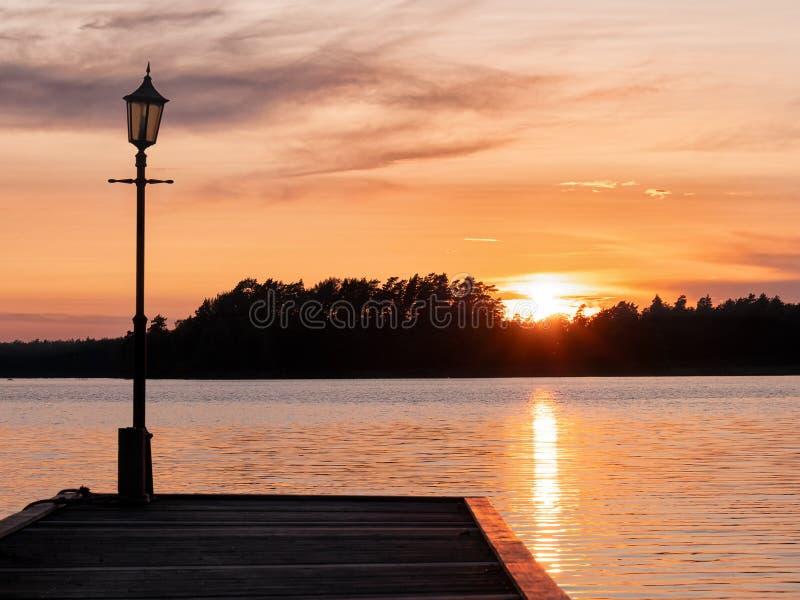 Εικόνα του Lakeside Sunset με ξύλινη προβλήτα και δέντρα στο φόντο στοκ εικόνες