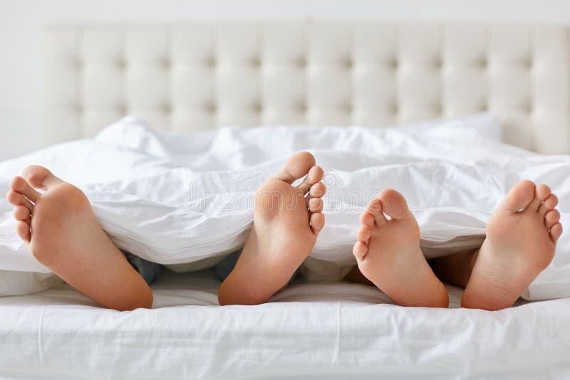 Εικόνα των γυμνών ποδιών ανδρών και γυναικών κάτω από το κάλυμμα στην κρεβατοκάμαρα Ο Unrecognizable σύζυγος και η σύζυγος περνού στοκ εικόνα