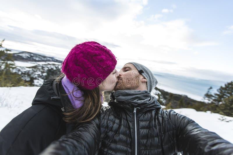 Εικόνα των ευτυχών νεολαιών ζευγών που αγαπούν έχοντας τη διασκέδαση στα χιονώδη βουνά στοκ εικόνα