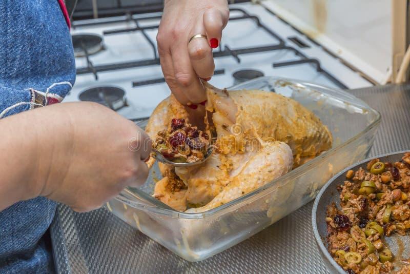 Εικόνα των θηλυκών χεριών που γεμίζουν ένα ακατέργαστο και φρέσκο ολόκληρο κοτόπουλο με το επίγειο κρέας που προετοιμάζεται με τι στοκ εικόνες