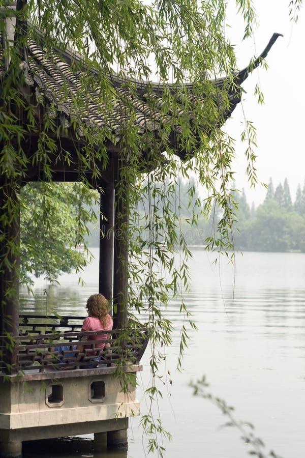 Εικόνα των νέων γυναικών που χαλαρώνουν στη λίμνη Xihu στοκ εικόνα