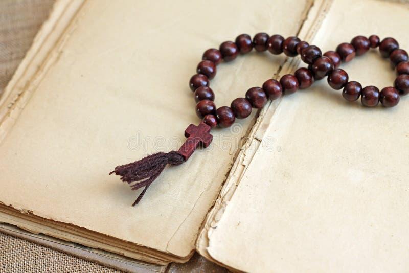 Εικόνα των ξύλινων rosary χαντρών που βρίσκεται στο ανοικτό βιβλίο στοκ φωτογραφίες