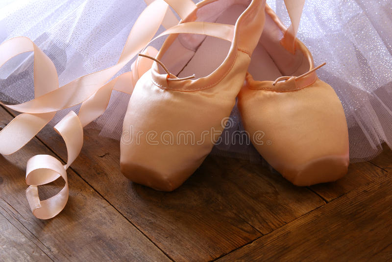 Εικόνα των παπουτσιών και του tutu μεταξιού pointe στο ξύλινο πάτωμα στοκ εικόνα με δικαίωμα ελεύθερης χρήσης