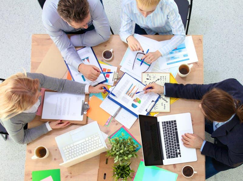 Εικόνα των συνέταιρων που συζητούν τα έγγραφα και τις ιδέες στη συνεδρίαση στοκ εικόνα