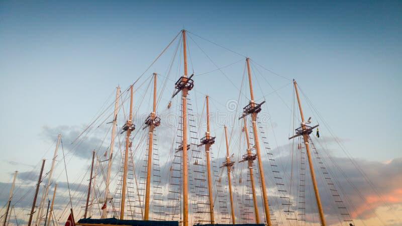 Εικόνα των υψηλών ξύλινων ιστών των παλαιών σκαφών στο λιμένα ενάντια στο μπλε ουρανό στο βράδυ στοκ εικόνες