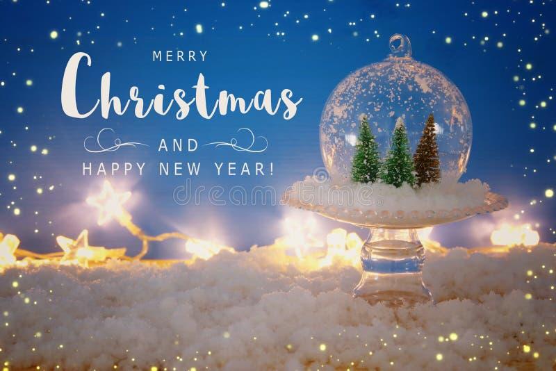 εικόνα των χριστουγεννιάτικων δέντρων μέσα στη σφαίρα γυαλιού πέρα από το χιονώδη ξύλινο πίνακα στοκ φωτογραφία