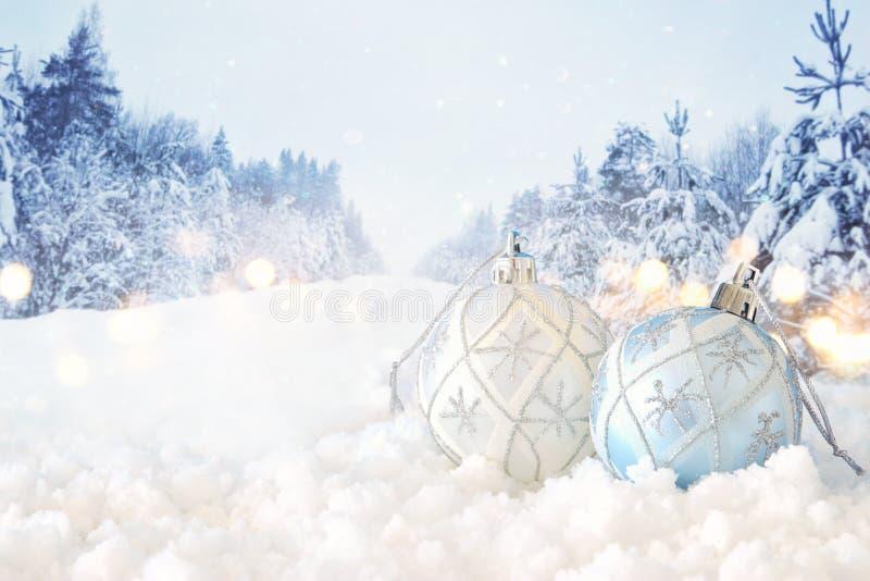 Εικόνα Χριστουγέννων της εορταστικής διακόσμησης σφαιρών δέντρων άσπρης μπροστά από το μαγικό υπόβαθρο χειμερινών τοπίων στοκ εικόνες