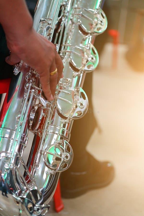 Εικόνες κινηματογραφήσεων σε πρώτο πλάνο των μουσικών που παίζουν Baritone Saxophone στο δωμάτιο πρακτικής μουσικής, θολωμένο υπό στοκ φωτογραφία με δικαίωμα ελεύθερης χρήσης