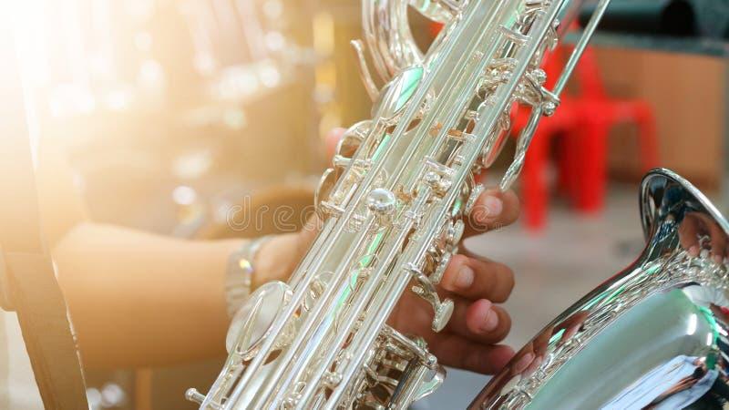 Εικόνες κινηματογραφήσεων σε πρώτο πλάνο των μουσικών που παίζουν Baritone Saxophone στο δωμάτιο πρακτικής μουσικής, θολωμένο υπό στοκ φωτογραφίες με δικαίωμα ελεύθερης χρήσης