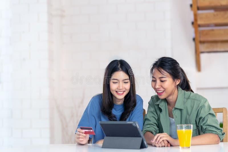 Ειλικρινής νέων ελκυστικών ασιατικών δύο κοριτσιών που κάθονται στο σπίτι να κρατήσει τη διαθέσιμη πληρωμή πιστωτικών καρτών έκπτ στοκ εικόνες με δικαίωμα ελεύθερης χρήσης