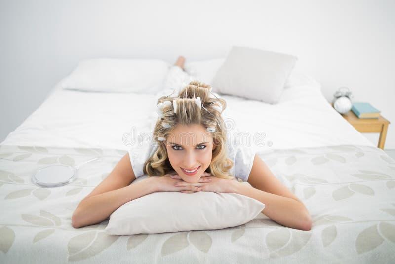Ειρηνικά αρκετά ξανθά φορώντας ρόλερ τρίχας που βρίσκονται στο κρεβάτι στοκ εικόνες
