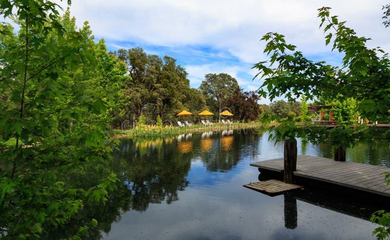 Ειρηνική στιγμή από μια λίμνη με την αποβάθρα και τις καρέκλες για να χαλαρώσει στοκ εικόνα