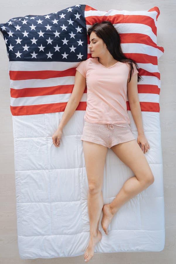 Ειρηνική συμπαθητική γυναίκα που βρίσκεται στη αμερικανική σημαία στοκ εικόνα