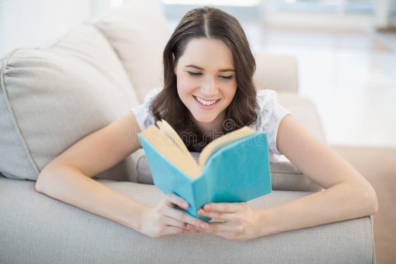 Ειρηνική όμορφη γυναίκα που βρίσκεται σε ένα άνετο βιβλίο ανάγνωσης καναπέδων στοκ εικόνες με δικαίωμα ελεύθερης χρήσης