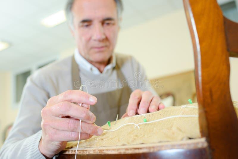 Ειρηνικός ανώτερος επιπλοποιός πορτρέτου που επισκευάζει την παλαιά καρέκλα στοκ φωτογραφίες με δικαίωμα ελεύθερης χρήσης