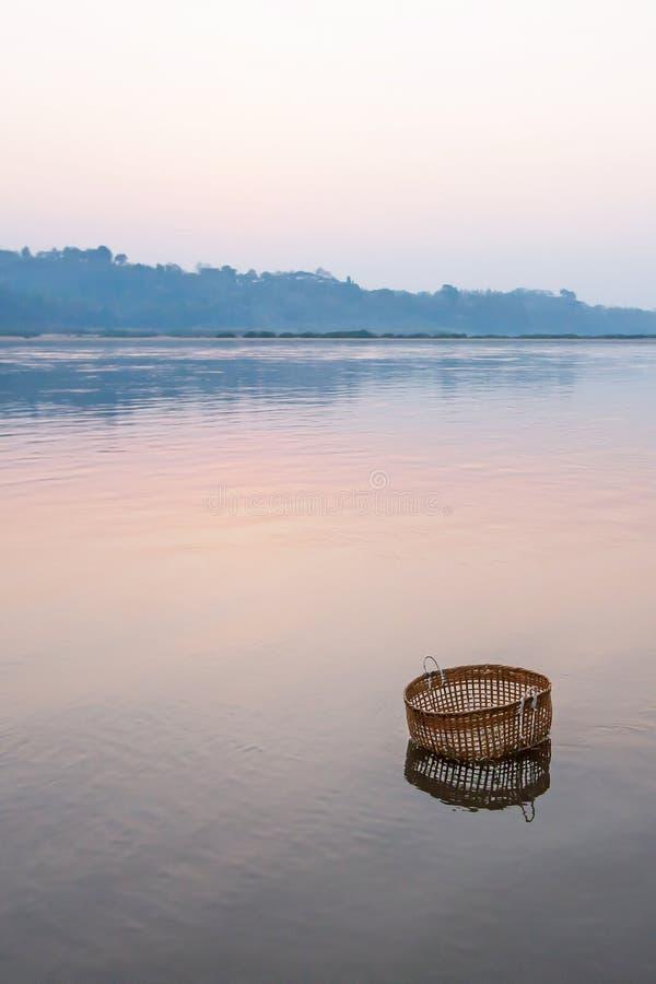 Ειρηνικός γαλήνιος από τον ποταμό, ένα καλάθι μπαμπού βυθίζει στο ποταμό Μεκόνγκ στο χειμερινό πρωί, ακόμα ζωή στο αγροτικό Λάος στοκ εικόνες