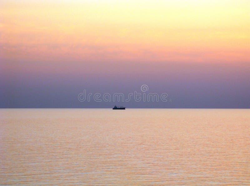 Ειρηνικός Ωκεανός με το σαφή ορίζοντα, τους πορφυρούς ουρανούς ηλιοβασιλέματος και το σκάφος στον ορίζοντα στοκ φωτογραφία με δικαίωμα ελεύθερης χρήσης