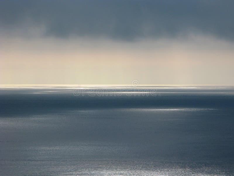 Ειρηνικός Ωκεανός με το σαφή ορίζοντα, δυσοίωνα σύννεφα, ετερόκλητες αντανακλάσεις του φωτός του ήλιου στοκ εικόνες