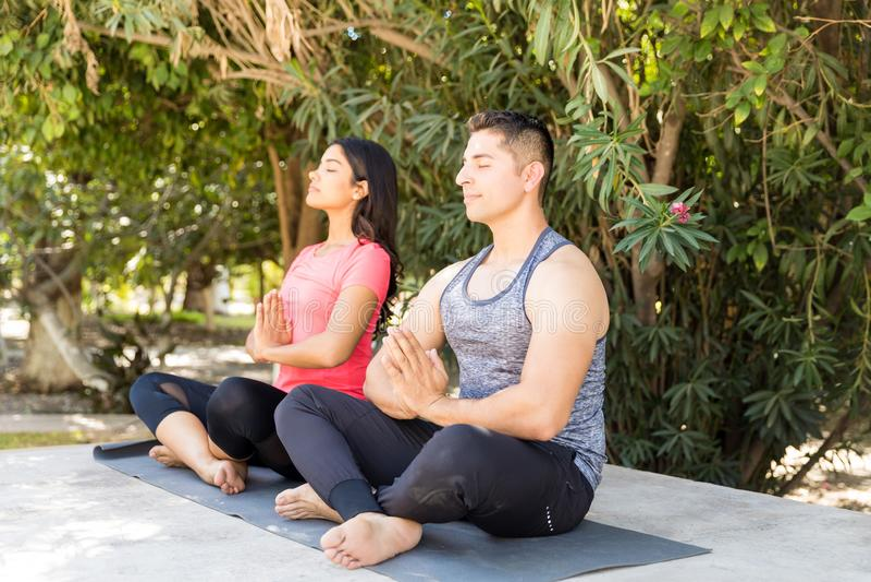 Ειρηνικό ζεύγος Meditating στο χαλί άσκησης στοκ εικόνα