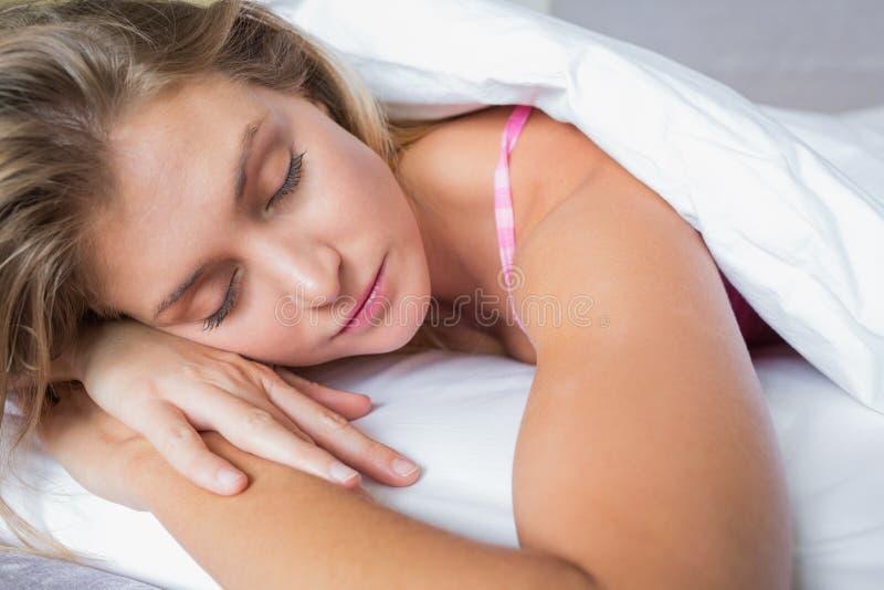 Ειρηνικό ξανθό να βρεθεί στο κρεβάτι της κοιμισμένο στοκ εικόνα
