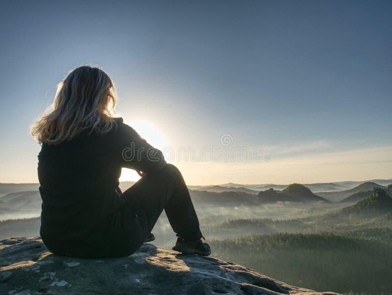 Ειρηνικό τοπίο το όμορφο κορίτσι κάθεται στους βράχους, κοιτάζει μακριά στοκ φωτογραφία