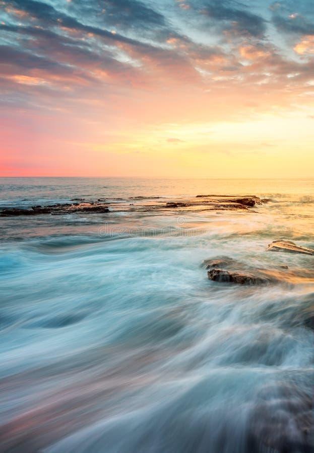 Εισερχόμενο πλύσιμο κυμάτων πέρα από τους βράχους στην ανατολή στοκ εικόνα