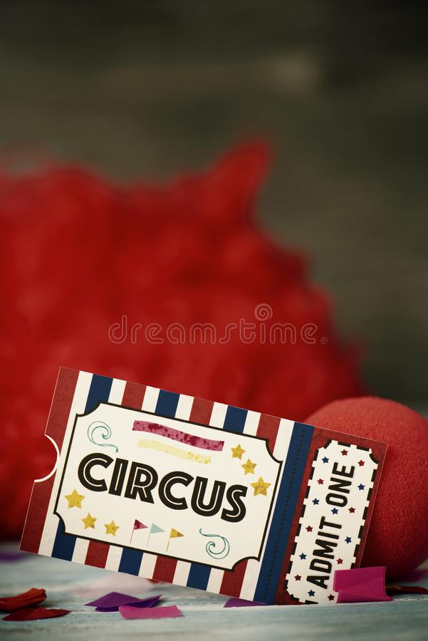 Εισιτήριο αποδοχής τσίρκων, μύτη κλόουν και κόκκινη περούκα στοκ φωτογραφίες