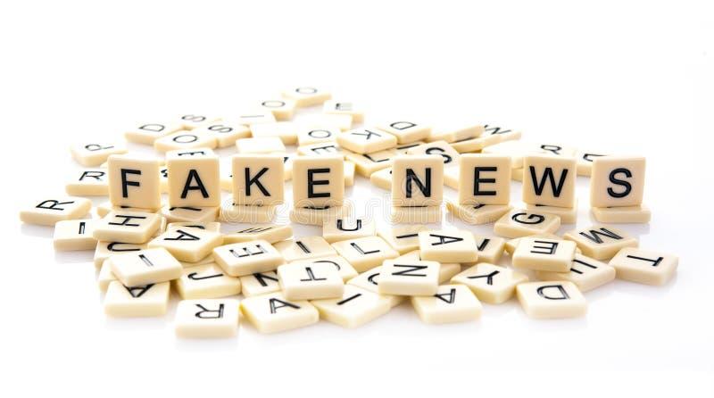 Ειδήσεις που εξηγούνται πλαστές στα κεραμίδια λέξης στοκ φωτογραφία με δικαίωμα ελεύθερης χρήσης