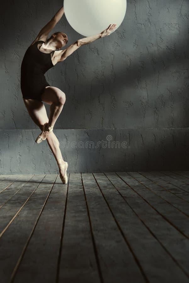 Ειδικευμένος νέος gymnast που εκτελεί χρησιμοποιώντας το άσπρο μπαλόνι στοκ φωτογραφία με δικαίωμα ελεύθερης χρήσης