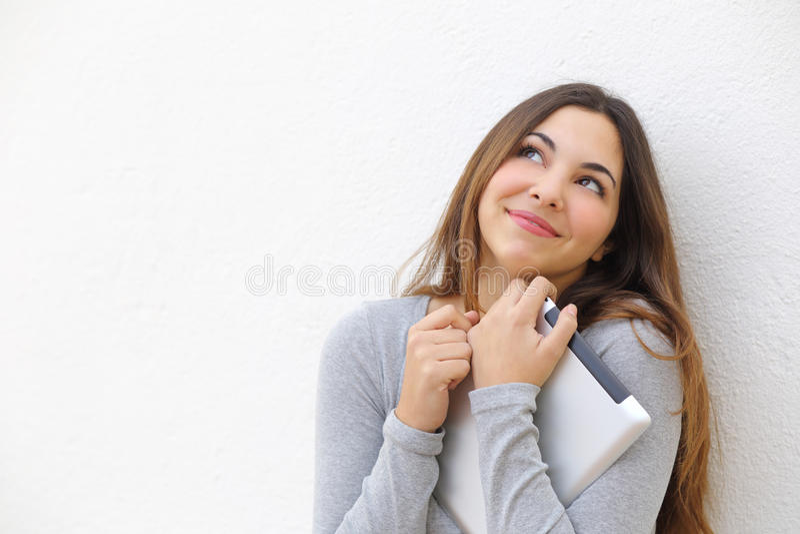 Ειλικρινές αθώο κορίτσι εφήβων που αγκαλιάζει μια ταμπλέτα και που κοιτάζει ανωτέρω στοκ εικόνες