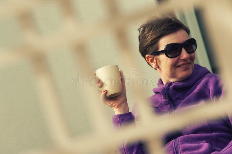 Ειλικρινής γυναίκα υπαίθρια με τον καφέ στοκ εικόνες