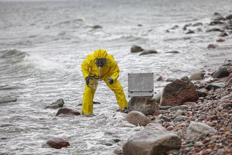 Ειδικός στο προστατευτικό κοστούμι που παίρνει το δείγμα του νερού στο εμπορευματοκιβώτιο στοκ εικόνες