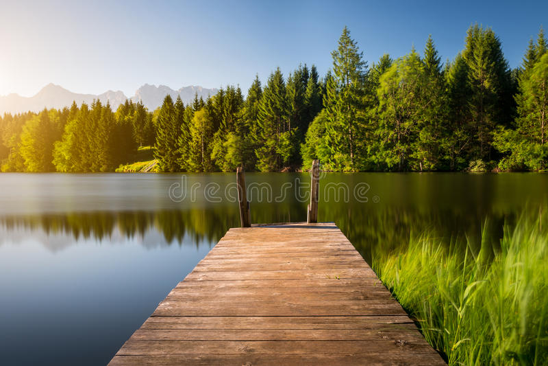 Ειδυλλιακή άποψη της ξύλινης αποβάθρας στη λίμνη με το υπόβαθρο τοπίου βουνών στοκ φωτογραφίες