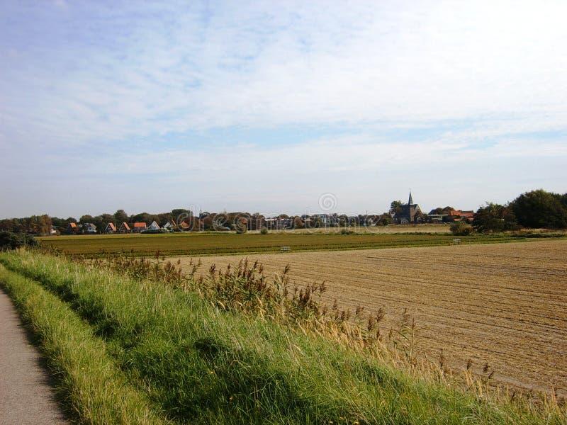 Ειδυλλιακή αγροτική άποψη του καλλιεργήσιμου εδάφους προσθηκών, στα όμορφα περίχωρα ενός μικρού χωριού χωριού στοκ φωτογραφία με δικαίωμα ελεύθερης χρήσης