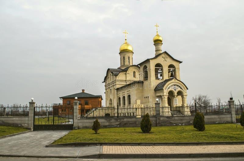Εκκλησία του ζωή-δίνοντας σταυρού του Λόρδου πίσω από το διακοσμητικό φράκτη επεξεργασμένος-σιδήρου ενάντια στο νεφελώδη ουρανό,  στοκ φωτογραφία