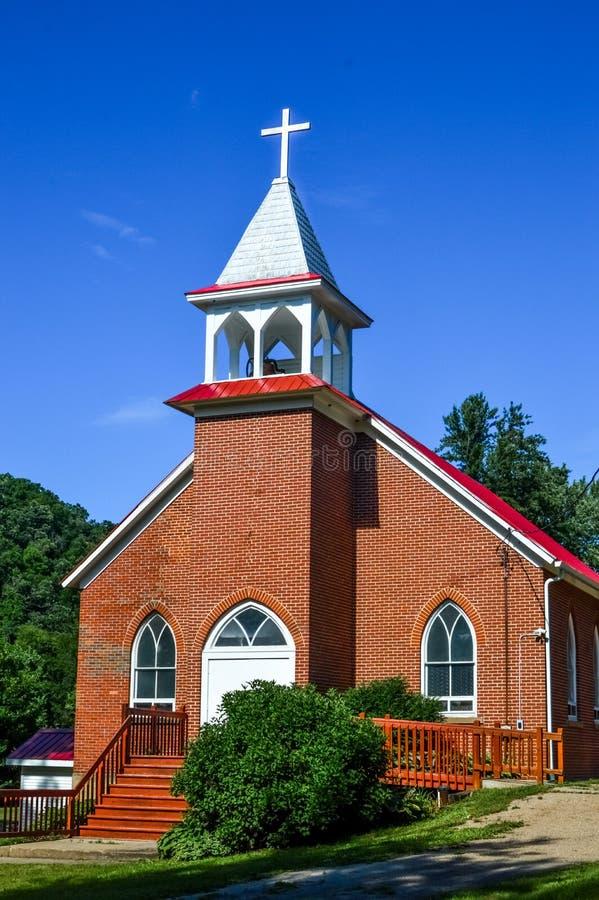 Εκκλησία τούβλου χώρας με το άσπρο διαγώνιο καμπαναριό στοκ εικόνες