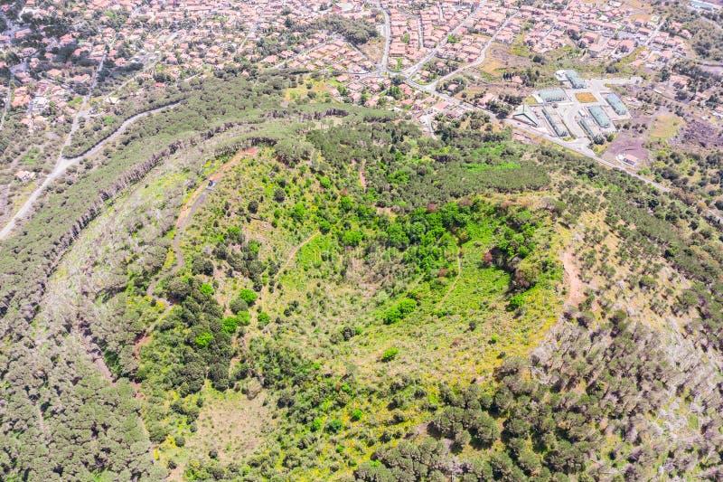 Εκλείψας αρχαίος κρατήρας ενός ηφαιστείου που καλύπτεται με το δάσος κοντά στην πόλη, εναέρια άποψη στοκ εικόνα με δικαίωμα ελεύθερης χρήσης