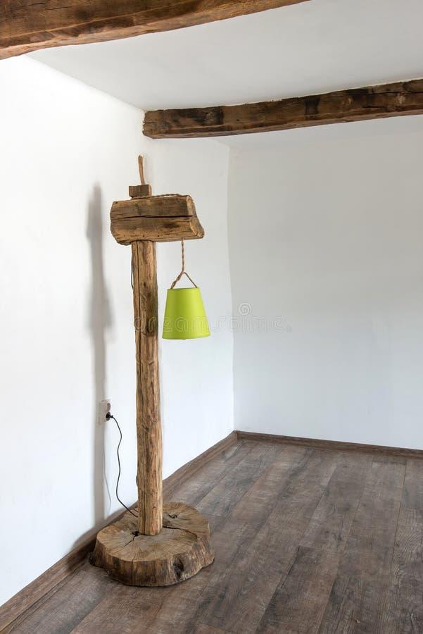 Εκλεκτής ποιότητας αγροτικός λαμπτήρας φιαγμένος από παλαιές ξύλινες ακτίνες και βάση κολοβωμάτων ενάντια στο άσπρο εσωτερικό σε  στοκ εικόνες