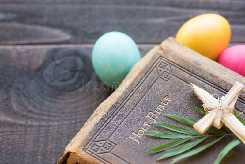 Εκλεκτής ποιότητας Βίβλος δέρματος με το σταυρό χλόης, φύλλα φοινικών, ζωηρόχρωμα αυγά Πάσχας στο σκοτεινό αγροτικό ξύλινο υπόβαθ στοκ εικόνες με δικαίωμα ελεύθερης χρήσης