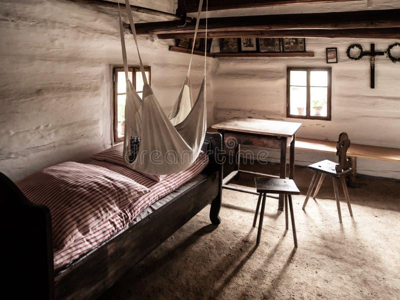 Εκλεκτής ποιότητας δωμάτιο με το κρεβάτι, τον πίνακα και τις καρέκλες στο παλαιό αγροτικό σπίτι Εικόνα ύφους σεπιών στοκ φωτογραφίες