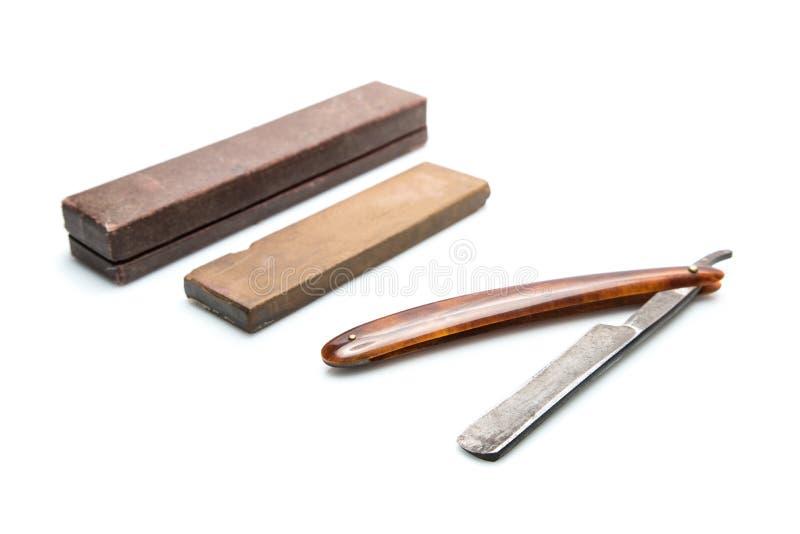 Εκλεκτής ποιότητας εξάρτηση ξυρίσματος, επικίνδυνο ξυράφι, πέτρα για το ακόνισμα των λεπίδων και της περίπτωσης, στο άσπρο υπόβαθ στοκ εικόνες