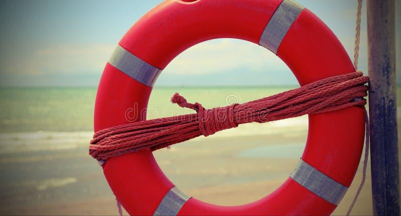 Εκλεκτής ποιότητας επίδραση με τον πορτοκαλή ζωή-σημαντήρα στην παραλία στοκ εικόνες