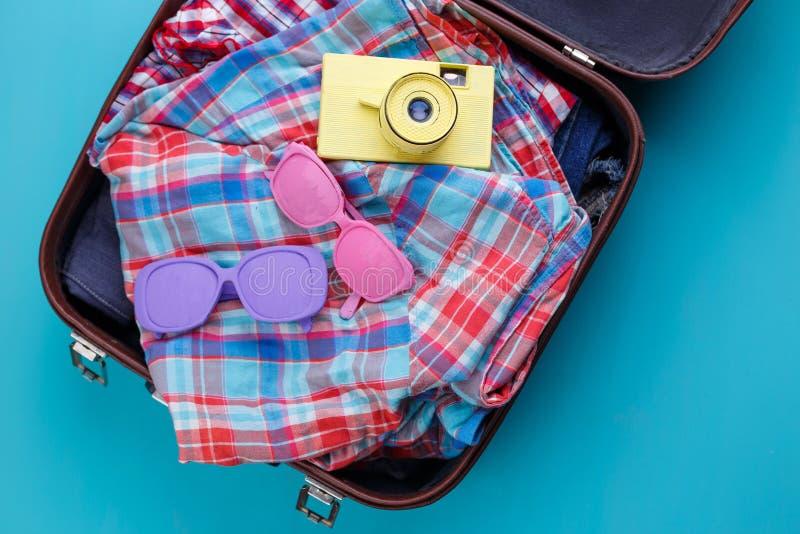 Εκλεκτής ποιότητας κάμερα, γυαλιά ηλίου και ελεγμένα πουκάμισα στην ανοικτή βαλίτσα στοκ φωτογραφία με δικαίωμα ελεύθερης χρήσης