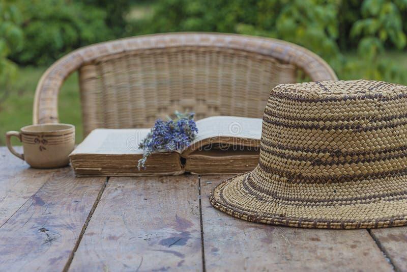 Εκλεκτής ποιότητας καπέλο αχύρου, παλαιό βιβλίο, φλιτζάνι του καφέ και ανθοδέσμη lavenders στον ξύλινο πίνακα με την ψάθινη καρέκ στοκ φωτογραφία με δικαίωμα ελεύθερης χρήσης