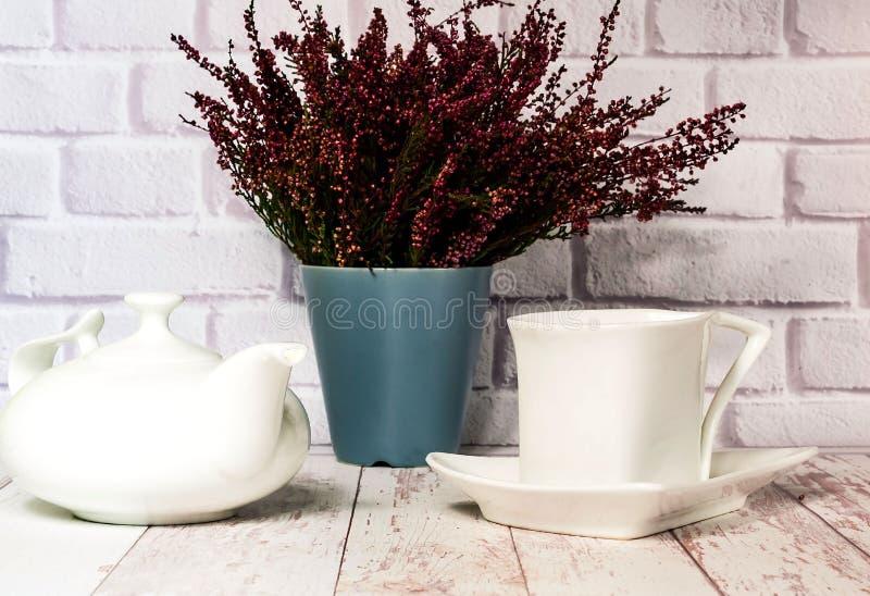 Εκλεκτής ποιότητας κεραμικά άσπρα φλυτζάνι και teapot στο άσπρο ξύλινο υπόβαθρο με την ερείκη, διάστημα αντιγράφων στοκ φωτογραφία με δικαίωμα ελεύθερης χρήσης