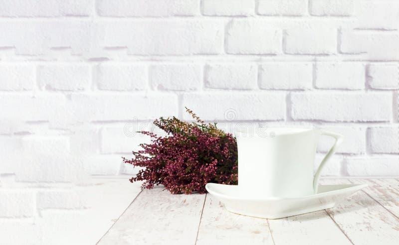 Εκλεκτής ποιότητας κεραμικό άσπρο φλυτζάνι στο άσπρο ξύλινο υπόβαθρο με την ερείκη στοκ εικόνες