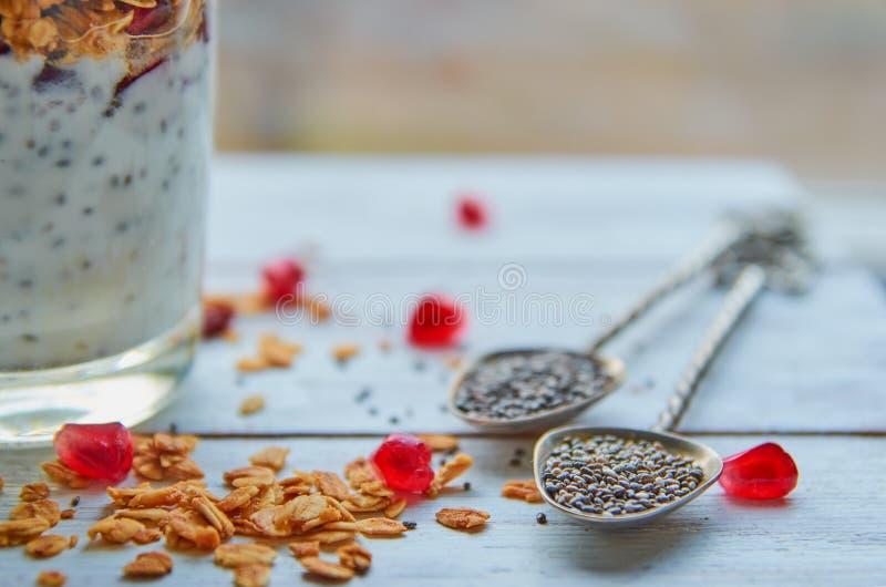 Εκλεκτής ποιότητας κουτάλια με το chia, τα διεσπαρμένους σιτάρια granola και τους σπόρους ροδιών στον άσπρο ξύλινο πίνακα Πουτίγκ στοκ φωτογραφία