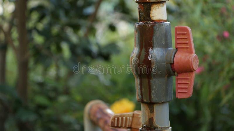 Εκλεκτής ποιότητας κόκκινη βαλβίδα υδροσωλήνων στον κήπο στοκ φωτογραφίες