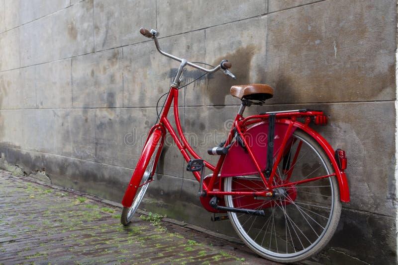 Εκλεκτής ποιότητας κόκκινο ολλανδικό ποδήλατο από ο παλαιός που σταθμεύει τοίχος πόλεων στοκ φωτογραφία με δικαίωμα ελεύθερης χρήσης